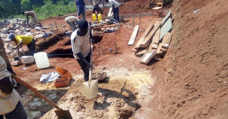 Builders at work on the latrines and foundation of ECD