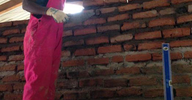 Een vrouwelijke metselaar in Malawi ...