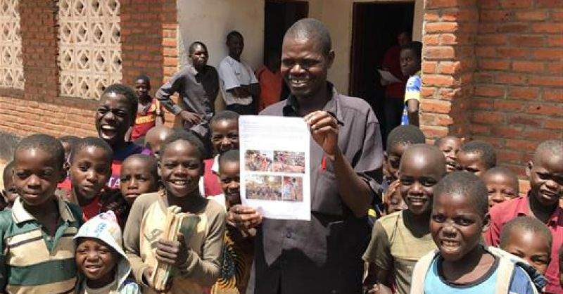Kinderen en docent bij de school